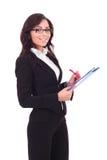 A mulher de negócio escreve na prancheta imagens de stock royalty free