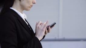 A mulher de negócio está andando com um telefone esperto filme