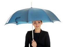 A mulher de negócio está guardando o guarda-chuva azul imagem de stock