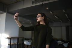 A mulher de negócio está levantando suas habilidades em uma faculdade privada elegante usando a conexão livre do wifi no terreno Fotografia de Stock