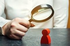 A mulher de negócio examina uma figura de homem vermelho através de uma lupa Análise das qualidades pessoais do empregado foto de stock royalty free