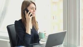 A mulher de negócio fala no telefone em seu escritório, datilografando no portátil