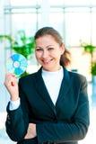 Mulher de negócio feliz nova com um CD à disposição Imagens de Stock