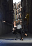 Mulher de negócio feliz nova que senta-se na cadeira do escritório na rua com portátil Fotos de Stock