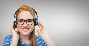 Mulher de negócio feliz que escuta a música contra o fundo cinzento Imagem de Stock Royalty Free