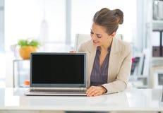 Mulher de negócio feliz que mostra a portátil a tela vazia imagem de stock royalty free
