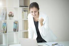 Mulher de negócio feliz que olha o computador com braços acima foto de stock