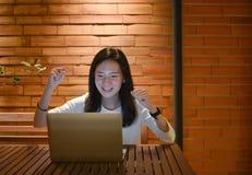 Mulher de negócio feliz que usa um portátil e trabalhando na noite fotografia de stock royalty free