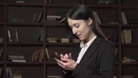 Mulher de negócio feliz que usa um smartphone filme