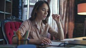 Mulher de negócio focalizada que trabalha no laptop no escritório domiciliário video estoque