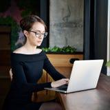 A mulher de negócio focalizada senta-se no funcionamento do café no portátil, no funcionamento fêmea sério concentrado com comput fotos de stock royalty free