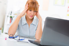 Mulher de negócio forçada que senta-se com sua cabeça em suas mãos Foto de Stock