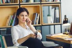 Mulher de negócio grávida que trabalha na conversa telefônica de assento da maternidade do escritório fotografia de stock royalty free