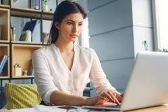 Mulher de negócio grávida que trabalha na datilografia de assento da maternidade do escritório no portátil imagens de stock