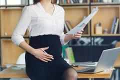 Mulher de negócio grávida que trabalha na maternidade do escritório que guarda o relatório imagem de stock royalty free