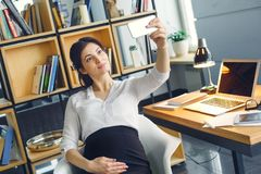 Mulher de negócio grávida que trabalha na maternidade do escritório que senta-se tomando fotos do selfie fotografia de stock royalty free