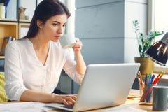 Mulher de negócio grávida que trabalha na maternidade do escritório que senta-se usando o chá bebendo do portátil imagens de stock royalty free