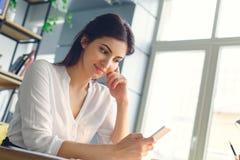 Mulher de negócio grávida que trabalha na maternidade do escritório que senta-se usando o smartphone imagem de stock royalty free