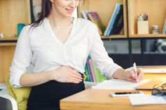 Mulher de negócio grávida que trabalha no close-up de assento da escrita da maternidade do escritório foto de stock
