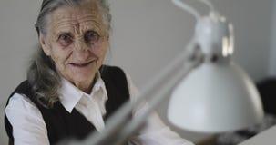 Mulher de negócio idosa com os enrugamentos profundos que trabalham atrás de um portátil no escritório video estoque
