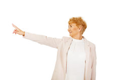 Mulher de negócio idosa do sorriso que aponta para o copyspace ou o algo Foto de Stock Royalty Free