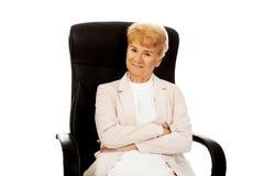 Mulher de negócio idosa do sorriso que senta-se na poltrona Fotografia de Stock Royalty Free