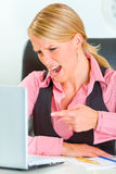 Mulher de negócio irritada na mesa que shouting no portátil Imagem de Stock Royalty Free