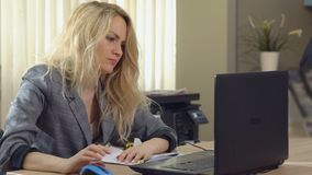 A mulher de negócio irritada no terno trabalha no computador no escritório vídeos de arquivo