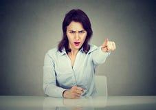 Mulher de negócio irritada que senta-se em apontar gritando da mesa com dedo a sair fotografia de stock royalty free
