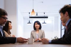 Mulher de negócio japonesa, chefe de projeto, assistindo à reunião imagens de stock royalty free