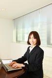Mulher de negócio japonesa nova com computer  Foto de Stock