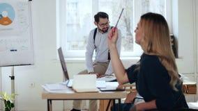 Mulher de negócio loura bonita nova feliz que pensa, lápis à disposição no escritório claro moderno, gerente masculino no fundo video estoque