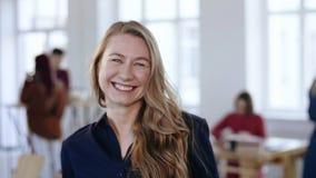 Mulher de negócio loura feliz na roupa formal que levanta, rindo e sorrindo alegremente no local de trabalho moderno na moda do e filme