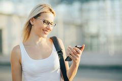 A mulher de negócio loura lê uma mensagem no telefone Foto de Stock