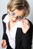 Mulher de negócio loura que ajusta vidros Fotografia de Stock