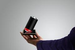 Mulher de negócio, mão que guarda um telefone do toque, com baixa bateria para fora Fotografia de Stock