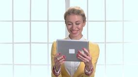 Mulher de negócio maduro que conversa com o alguém que usa a tabuleta video estoque