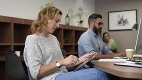 Mulher de negócio maduro que usa a tabuleta digital no escritório filme