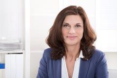 Mulher de negócio mais idosa bem sucedida que senta-se no escritório. imagens de stock royalty free