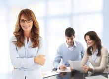 Mulher de negócio moderna com colegas Imagens de Stock Royalty Free