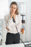 Mulher de negócio moderna pensativa que guarda o telefone Imagem de Stock Royalty Free