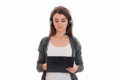 A mulher de negócio moreno adorável nova com fones de ouvido e o microfone fazem as anotações isoladas no fundo branco Imagem de Stock Royalty Free