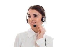 Mulher de negócio moreno bonita nova com fones de ouvido e microfone que sorri e que olha isolada afastado no branco Imagem de Stock