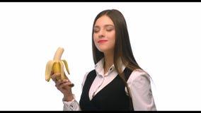 Mulher de negócio moreno bonita que guarda uma banana em um fundo branco filme