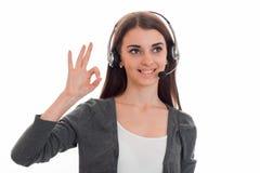 Mulher de negócio moreno do cutie novo com fones de ouvido e microfone que sorri e e que mostra isolado ESTÁ BEM no branco Fotos de Stock Royalty Free