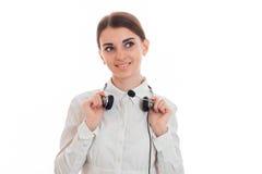 Mulher de negócio moreno do cutie novo com fones de ouvido e microfone que sorri e que olha isolada afastado no fundo branco Imagem de Stock