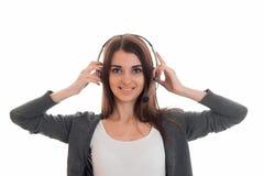 Mulher de negócio moreno encantador nova com os fones de ouvido e o microfone que olham a câmera e o sorriso isolados sobre Imagem de Stock