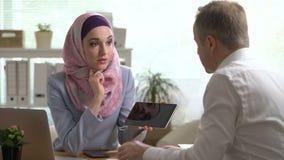 Mulher de negócio muçulmana nova e homem caucasiano que trabalham com a tabuleta no escritório video estoque