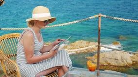 Mulher de negócio no feriado, sentando-se em um café com vistas cênicos do mar Trabalha com tabuleta filme