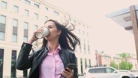 Mulher de negócio no fundo do café bebendo e de olhar da cidade da manhã o telefone O vento está fundindo com seu hai video estoque